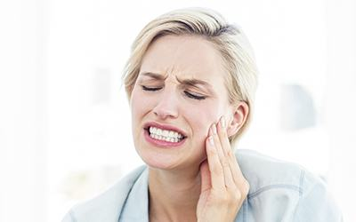 Grimacing woman in pain holding cheek