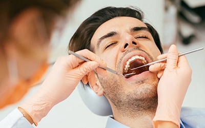 Relaxed man in dental chair receiving root canal