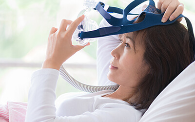 Woman in bed with sleep apnea appliance