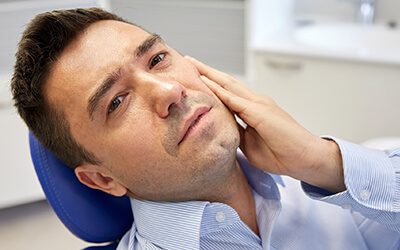 Man in dental chair showing jaw pain